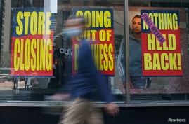 People walk past a business that is closing following the outbreak of COVID-19 in the Manhattan borough, New York, Aug. 17, 2020.