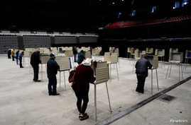 Voters cast their ballots at socially distanced privacy booths at a early voting site inside the Bismarck Event Center as the coronavirus disease (COVID-19) outbreak continues in Bismarck, North Dakota, Oct. 26, 2020.