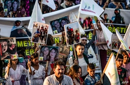 Syrian Yazidis march with pictures and banners during a demonstration in the northeastern town of Amude, about 28 kilometres…