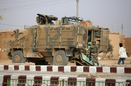 A Turkish soldier stands near his armoured vehicle on a highway near the northern Syrian town of Ain Issa in the countryside of…