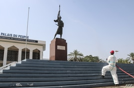 A firefighter sprays disinfectant on the statue of the warrior of independence in front of the People's Palace, a public…