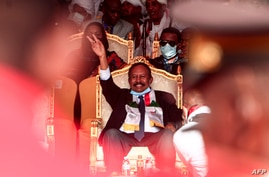Sudan's Prime Minister Abdalla Hamdok (C) flashes the victory sign while seated during a reception ceremony in the capital…