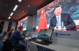 Journalists sit next to the screens showing Chinese President Xi Jinping delivering a speech via video for the opening ceremony…