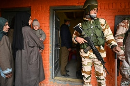 An Indian paramilitary soldier stands guard as voters stand in a queue to cast their ballots during the second phase of the…
