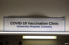 A signs in the Covid-19 Vaccination Clinic at the University Hospital in Coventry, central England is pictured on December 4,…