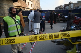 Security officials inspect the site of an explosion at a Ganj Mandi bazar in Rawalpindi on December 13, 2020. - At least 20…