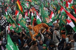 Supporters of Pakistan Democratic Movement (PDM) gather during an anti-government rally in Lahore on December 13, 2020. (Photo…