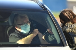 A patient receives an injection of their first dose of the Pfizer-BioNTech Covid-19 vaccine in their car at a drive-in…