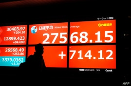 A pedestrian walks past an electronic quotation board displaying share prices of the Tokyo Stock Exchange in Tokyo on December…