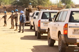 Members of the United Nations and African Union peacekeeping mission (UNAMID) gather with their vehicles in Kalma camp for…