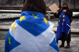 An anti-Brexit pro-Scottish independence activist wrapped in an EU flag holds a placard during a small protest against Britain…