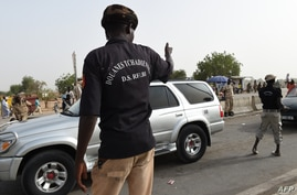 Chadian customs officers control a car on April 4, 2015 on the N'Gueli bridge, marking the border between Chad and Cameroon…