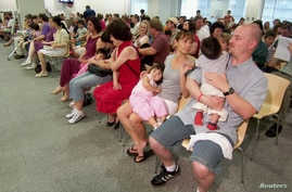 Couples from the U.S. wait at the U.S. embassy to get visa packs for their newly adopted Chinese children in Guangzhou, south…