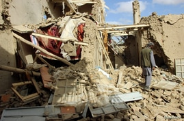 An Afghan man inspects a house destroyed during an air strike called in to protect Afghan and U.S. forces during a raid on…