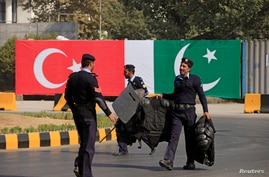 Policemen walk near the national flags of Pakistan and Turkey displayed along a road ahead of a visit of Turkish President…