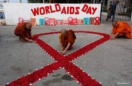 Buddhist monks light candles during an HIV/AIDS awareness campaign on the occasion of World AIDS Day in Kolkata, India.