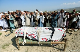 Relatives and residents pray near a coffin during a funeral ceremony of one of the victims after a drone strike, in Khogyani…