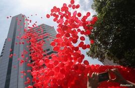 Red balloons are released ahead of World AIDS Day at the Emilio Ribas Hospital in Sao Paulo, Brazil, Nov. 29, 2019.