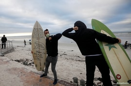 Surfers bump elbows as they protest against the nationwide lockdown regulations that allow exercise but not water activities,…
