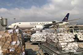Staff members of King Salman Humanitarian Aid and Relief Center unload humanitarian aid at Beirut International airport to…