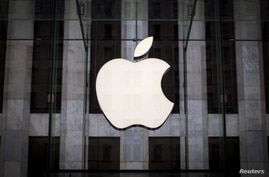 FILE PHOTO: An Apple logo hangs above the entrance to the Apple store on 5th Avenue in the Manhattan borough of New York City,…