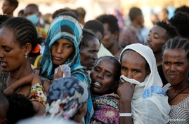Ethiopian refugees stand in for supplies at the Um Rakuba refugee camp which houses refugees fleeing the fighting in the Tigray…
