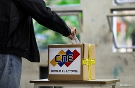 A man casts his vote at a polling station during parliamentary election in Caracas, Venezuela, December 6, 2020. REUTERS…