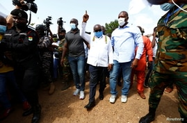 Ghana's President Nana Akufo-Addo gestures at a polling station during presidential and parliamentary elections in Kyebi, Ghana…