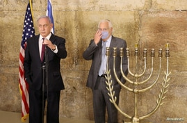 FILE - Israeli Prime Minister Benjamin Netanyahu (L) and U.S. Ambassador to Israel David M. Friedman light the first Hanukkah at the Western Wall in Jerusalem's Old City during the the Jewish holiday of Hanukkah, Dec. 10, 2020.
