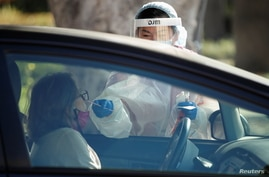A healthcare worker at LAC USC Medical Center tests a person at a drive through testing center during the outbreak of the…