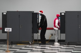 People cast their ballots in the U.S. Senate runoff elections on the first day of early voting in Atlanta, Georgia, U.S.,…