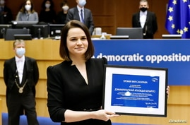 Belarus' opposition leader Sviatlana Tsikhanouskaya poses with the Sakharov Prize, European Union's annual human rights award,…