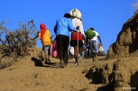 Ethiopians, who fled the ongoing fighting in Tigray region, carry their belongings after crossing the Setit River on the Sudan…