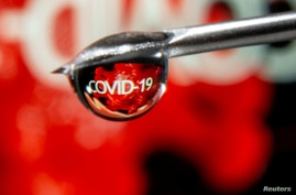 "FILE PHOTO: The word ""COVID-19"" is reflected in a drop on a syringe needle in this illustration taken November 9, 2020. REUTERS…"