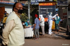 A healthcare worker wearing personal protective equipment (PPE) collects a swab sample from a man, amidst the spread of the…