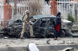A member of Afghan security forces inspects a damaged vehicle at the site of a blast in Kabul, Afghanistan December 20, 2020…
