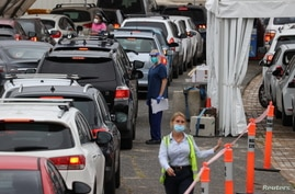 Vehicles queue while medical personnel administer tests for the coronavirus disease (COVID-19) at the Bondi Beach drive-through…