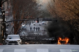A vehicle burns near the site of an explosion in the area of Second and Commerce in Nashville, Tennessee, Dec. 25, 2020.