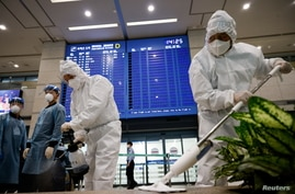 Workers wearing protective gear disinfect an arrival gate as an electronic board shows arrivals' information amid the…