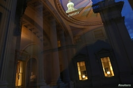 Office lights are seen at the U.S. Capitol as lawmakers work into the evening while the U.S. Senate face a decision over…