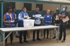 Observers from the African Union examine ballots at the Ridge Church polling center in Accra, Ghana, Dec. 7, 2020.