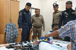 One of seven men arrested for human trafficking in Thailand Tuesday sits on his bed alongside several handguns, a sign of the dangers in and around Thailand's ports where big money is to be made off the backs of cheap labor. (Courtesy DSI)
