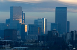 FILE - In this Thursday, Feb. 28, 2019, file photograph, pollution obscures the skyline of downtown as the sun rises over…