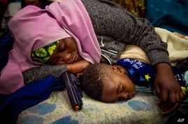 FILE - A mother sleeps with her child holding a toy gun, outside the UN refugee agency in Cape Town, South Africa, Oct. 10, 2019.