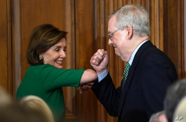 House Speaker Nancy Pelosi of Calif., left, and Senate Majority Leader Mitch McConnell of Ky., right, bump elbows as they…