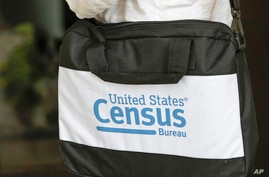 A briefcase of a census taker is seen as she knocks on the door of a residence Tuesday, Aug. 11, 2020, in Winter Park, Fla. A…