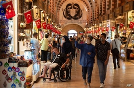 People wearing masks for protection against the spread of coronavirus, walk in the Spice Market, or the Egyptian Bazaar, in Istanbul, Sept. 11, 2020.