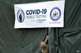 A member of the National Guard assisting at a COVID-19 mobile testing location looks out of a tent used for drive-thru tests,…