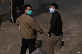 Hong Kong activists Joshua Wong, right, and Ivan Lam, left, are escorted by Correctional Services officers to prison, in Hong…