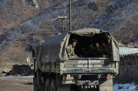 Azerbaijani soldier soldiers sit in a military truck on a road to their military tent camp, Kalbajar, Azerbaijan, Dec. 2, 2020.